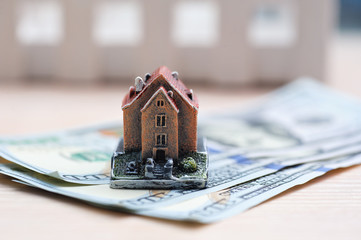 Many dollar banknotes and a house model; concept of buying a hou