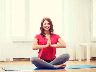 smiling redhead teenager meditating at home