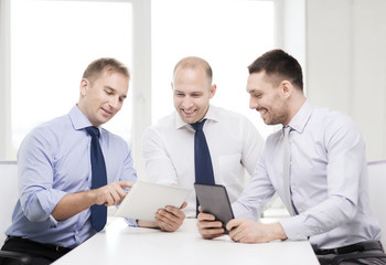three smiling businessmen with tablet pc in office