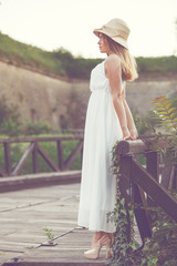 Beautiful young woman in an elegant white dress with a hat on hi