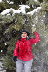Black-haired Turkish women playing under the snowy branches