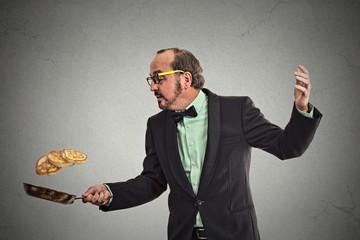 smiling man tossing pancakes on frying pan grey background