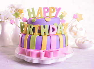 Delicious birthday cake on table on brick wall background
