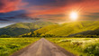 canvas print picture - abandoned road through meadows in mountain at sunset
