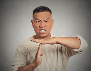 Angry man showing time out gesture on grey wall background
