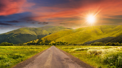 abandoned road through meadows in mountain at sunset