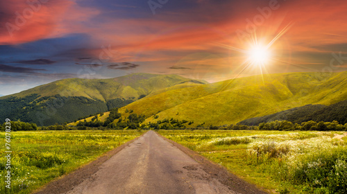 canvas print picture abandoned road through meadows in mountain at sunset