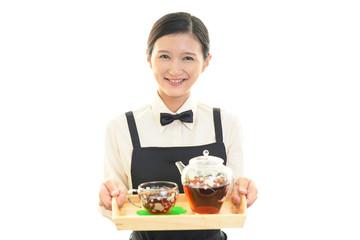 紅茶を運ぶ笑顔のウェイトレス