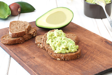 avocado dip (guacamole) on bread on cutting board