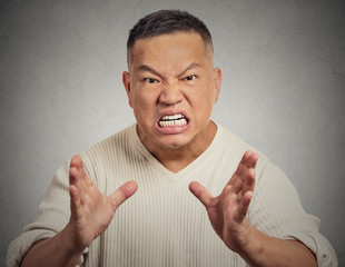 Angry man screaming isolated on grey wall background