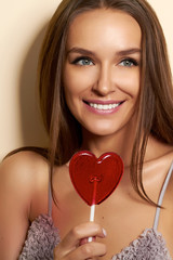 Lovely woman smiling covers one eye lollipop red heart.