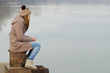 Lonely teenage girl sitting on the dock on cold winter day