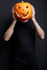 Halloween pumpkin on man head on black, clipping path