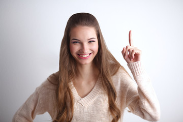 Portrait of a smiling young woman pointing up