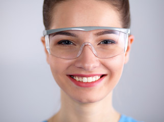 Pretty woman doctor in glasses smiling,  standing on gray