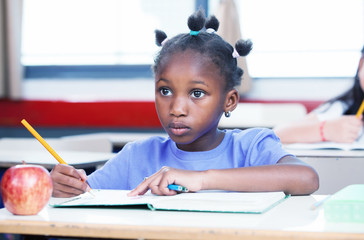 Afro american girl in primary school classroom writing her book