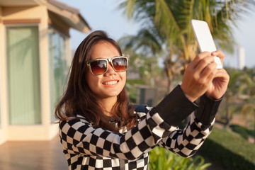 portrait of young beautiful woman wearing sun glasses take a pho