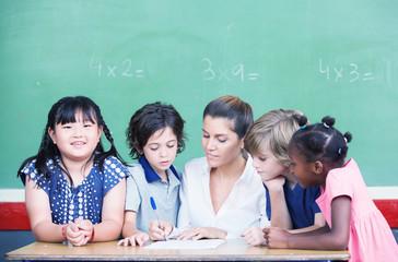 Multi ethnic classroom with teacher explaining mathematics lesso