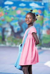 Happy afro american elementary female student entering school