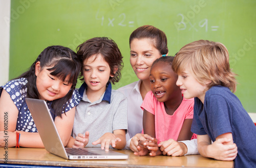 Leinwandbild Motiv Interracial primary classroom learning to use laptop with their