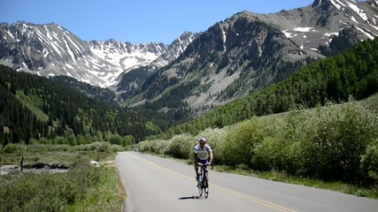 Lone Cyclist on bicycle riding in the mountains