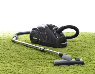 Powerfull black Vacuum cleaner on green carpet floor