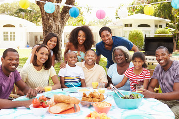 Multi Generation Family Enjoying Meal In Garden Together