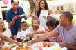 Multi Generation Family Enjoying Meal In Garden Together - 76082803