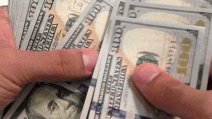 Close-up of a businessman's hands counting hundred dollar bills