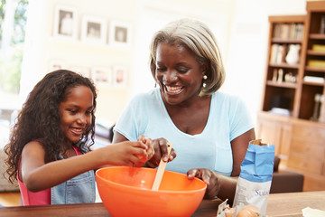 Grandmother And Granddaughter Baking Together At Home