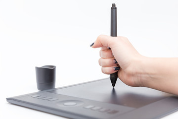 black graphic tablet and hand with force holds the pen