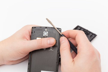 black phone in  hand and a screwdriver
