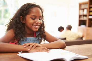 Girl Reading Book For Homework At Table