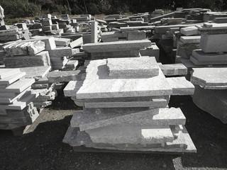 Stacks of granite slabs in a yard under sunlight