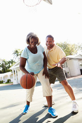 Senior Couple Playing Basketball Together