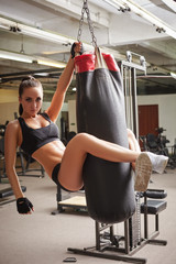 Pretty young woman hanging on punching bag