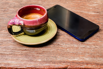 An elephant cup of espresso on wooden background and smart phone