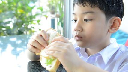 Little asian boy eating hamburger .