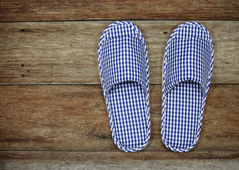 blue and white home slippers on wood floor