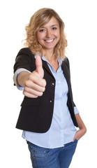 Frau mit blonden Locken und Blazer zeigt den Daumen