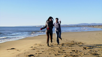 Happy couple on beach in winter running slow motion playful