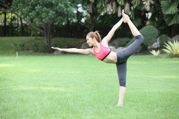Young woman practicing yoga, standing bow pose on lawn