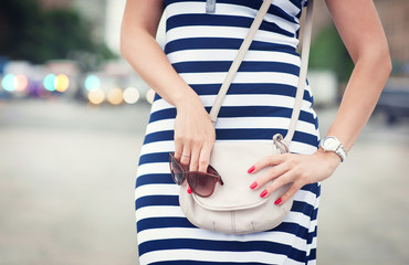 Fashionable woman with bag in her hands and striped dress