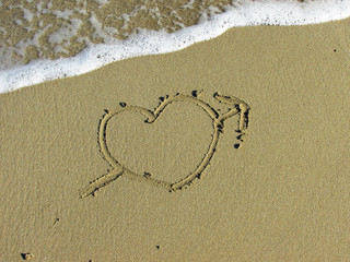 Heart pierced by an arrow drawn in the sand