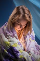 The girl sits having turned back a blanket
