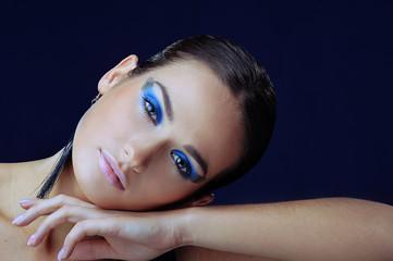 Beautiful girl with blue festive make-up in long earrings