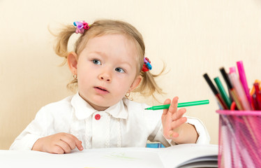Cute child girl drawing with pencils in kindergarten