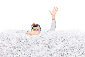 Man diving in a pile of shredded paper