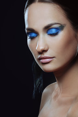 Beautiful girl with blue festive makeup closed her eyes