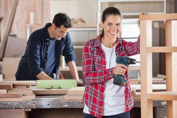 Happy Female Carpenter Drilling Wood In Workshop